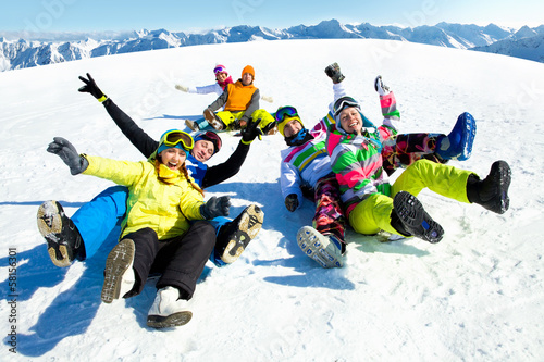 friends slide downhill together on mountain holiday