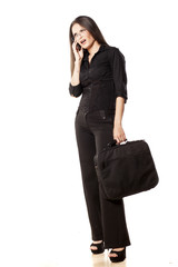 Sulky woman holding a laptop bag and talking on the phone