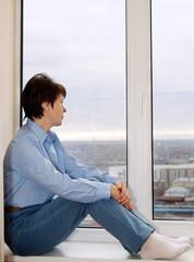 Woman sitting on a windowsill and awaiting