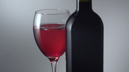 red wine being dropped into glass shot in super slow motion