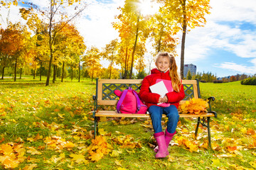 Autumn portrait of little girl on the bench