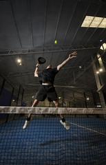 Paddle tennis player smashing, full length.