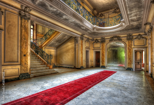 Leinwanddruck Bild Red carpet in the hallway of an abandoned manor