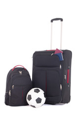 suitcase with passports, backpack and soccer ball isolated on wh