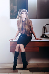 Fashion woman sits on washstand