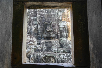 An ancient king face outside the window of temple in angkor thom
