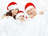 Christmas family and baby in Santa Claus hat lying over white