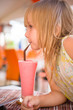 Adorable girl drink pink shake in restaurant