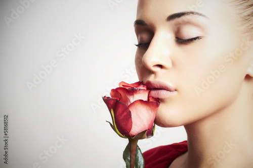 Girl and flower. beautiful woman in red dress.close-up
