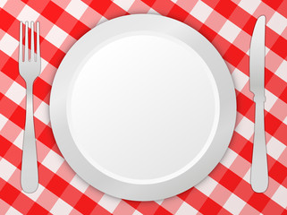 Fork, knife and plate on tablecloth