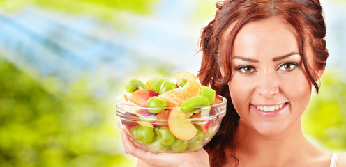Young woman holding glass bowl with fruit salad