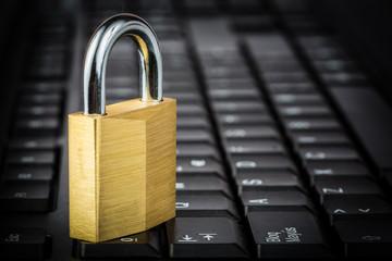 Closed golden padlock on a black computer keyboard