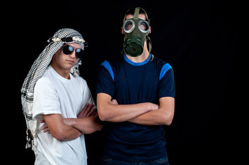 Young Arab with sunglasses and a young man with gas mask