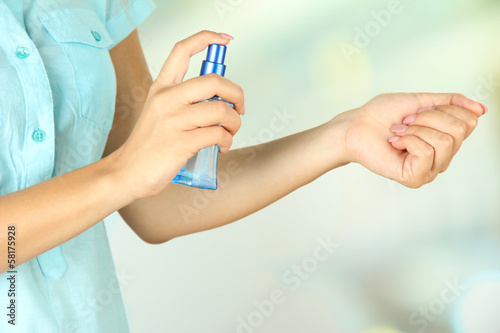 Woman testing perfume on natural background