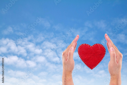 Heart sign velvet  in Hand on blue sky