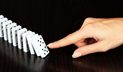 Hand pushing dominoes on wooden background