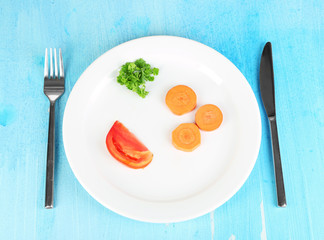Small portion of food on big plate on wooden table close-up