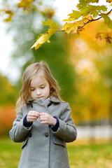 Adorable little girl having fun on autumn day