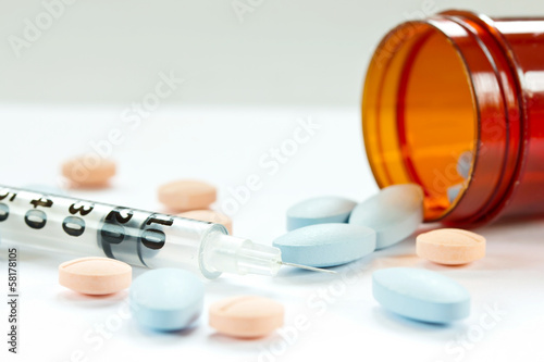 Pills spilling out of pill bottle and Syringe isolated on white