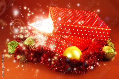 Gift box with bright light on it on red background