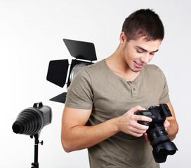 Handsome photographer with camera, on photo studio background