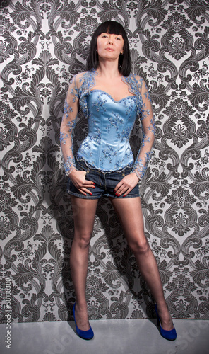 woman in blue corset and stockings posing against wall