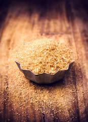 Brown sugar for a Christmas baking in a bowl on wooden table, se
