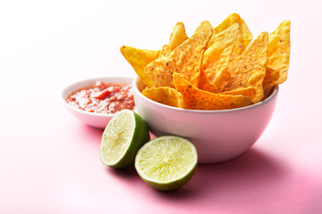 Bowl of Nachos, Salsa and Lime on a Pink Background
