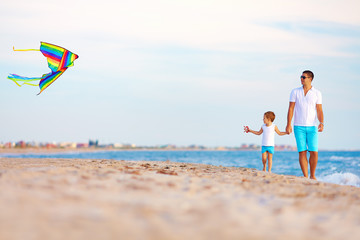 happy father and son playing with kite on summer beach