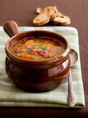 closeup of hot lentil soup with carrots and bacon