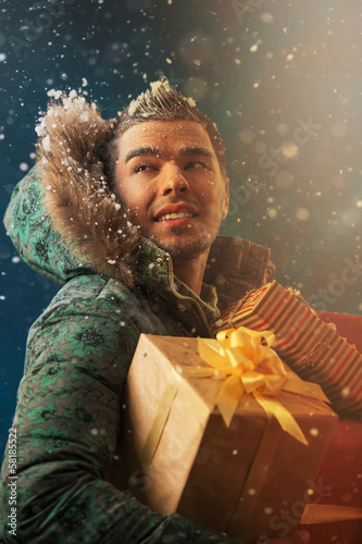 Bright picture of handsome man carrying Christmas Gifts outdoors