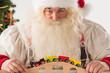 Santa Claus sitting and playing with railway toy at home