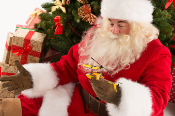 Portrait of happy Santa Claus holding gift helicopter toy