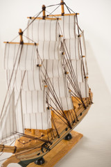 Wooden ship toy model on white table against white background