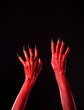 Red spooky devil hands with black nails, real body-art