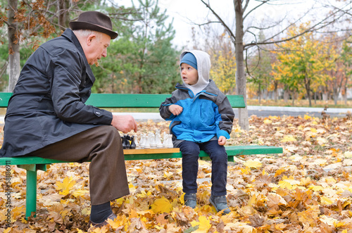 Grandfather playing chess with his little boy