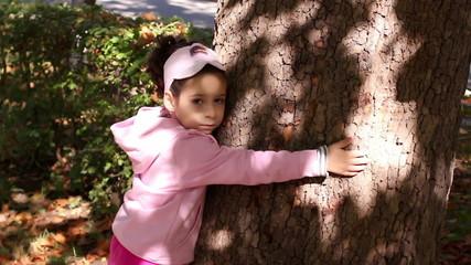 I love nature.Cute little girl hugging big tree in park