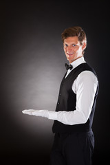 Male Waiter Presenting Something
