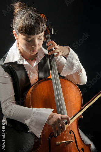 Girl with cello on black background