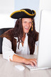 Happy Pirate Using Computer