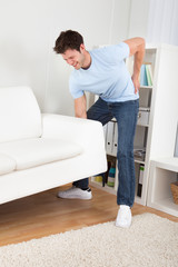 Man In Pain Lifting Couch
