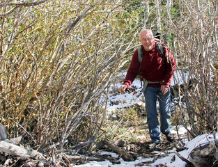senior man hiking in snowy trees