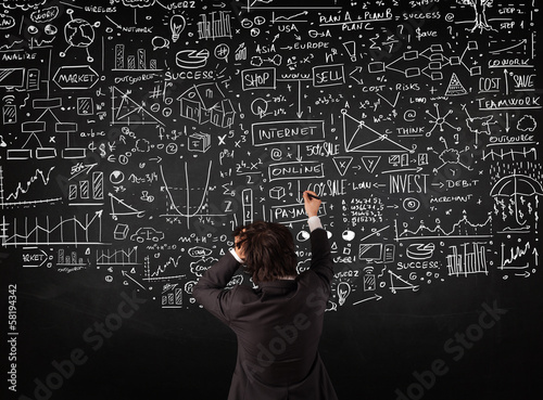 Businessman standing in front of drawn charts on a blackboard
