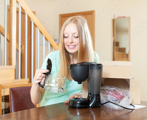 Cheerful woman unpacking and reading manual for new coffeemaker