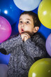 Birthday, child surrounded by balloons at a party
