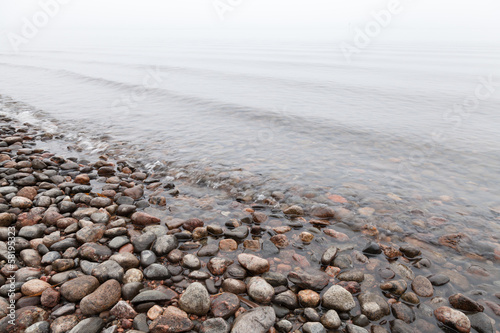 Stones on Saimaa lake coast in foggy morning