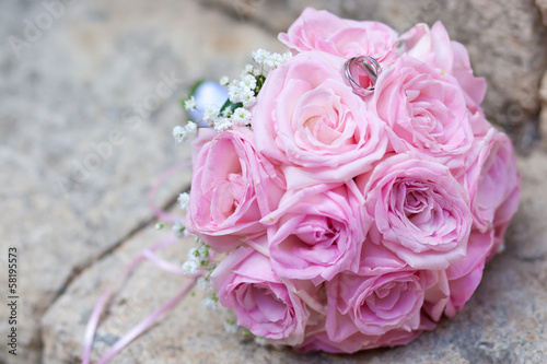silver wedding rings on wedding bouquet of pink roses
