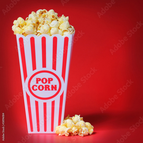 Popcorn in box over red background