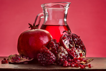 pomegranate isolated on a white with juice in the jug