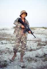 Young female soldier dressed in a camouflage with a gun in the o